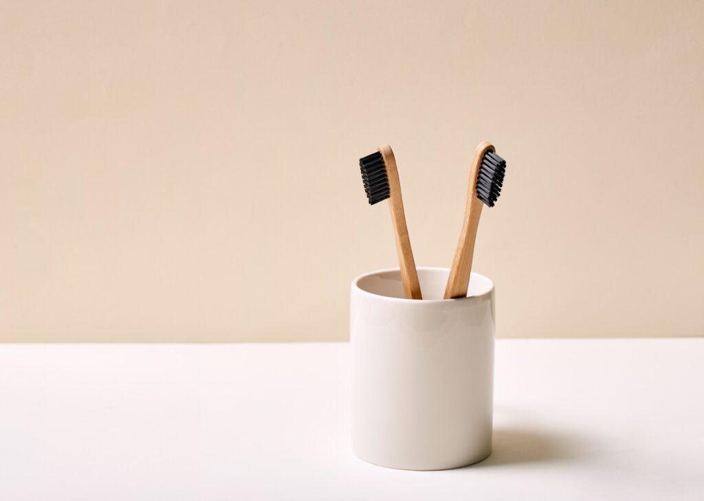 Two bamboo toothbrushes in a white holder